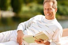 Agreeable man reading a book Stock Photos