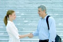 The agreement. Bussiness woman shakes hand with a fellow business man in front of some sober marble stairs Stock Photo