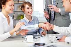 Agreement. Image of business partners making an agreement with woman clapping her hands near by Stock Image