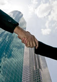 In agreement. A handshake taken against a sky with tall beautiful glass towers of commerce filling the background Royalty Free Stock Image