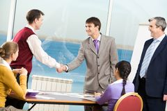 Agreement. Businessmen handshaking after signing documents at meeting Royalty Free Stock Image
