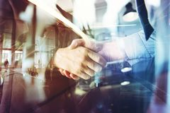 Handshaking business person in the office. concept of teamwork and partnership. double exposure royalty free stock photo