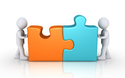 Agreement concept with puzzle pieces. Two businessmen connect different colored puzzle pieces Royalty Free Stock Image