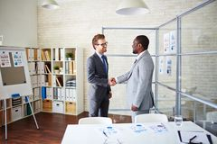 Agreement. Confident managers handshaking in office after signing contract Royalty Free Stock Images