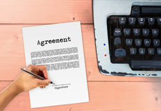 Agreement with hand signing signature. Vintage contract typewriter Royalty Free Stock Photos