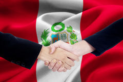 Agreement handshake with flag of Peru. Picture of agreement handshake with two businesspeople hands, shaking hands with Peru flag background Royalty Free Stock Photography