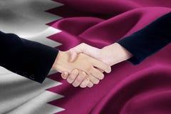 Agreement handshake with flag of Qatar Stock Photo