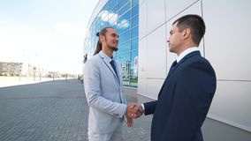Agreement, handshake two businessmen, shaking hands high definition video. Businessmen shaking hands against the background of the office center stock video footage