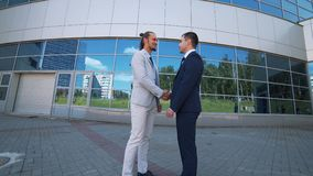 Agreement, handshake two businessmen, shaking hands high definition video. Businessmen shaking hands against the background of the office center stock footage