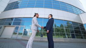 Agreement, handshake two businessmen, shaking hands high definition video. Businessmen shaking hands against the background of the office center stock video