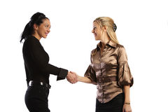 Agreement made. Blonde and brunette business girls come to agreement and shake hands to close the deal Stock Images