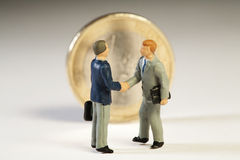 Agreement Among Member States On European Debt. Two miniature figurines of businessmen shake hands in front of an upright Euro coin on new treaty proposals Royalty Free Stock Photography