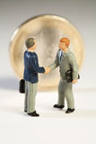 Agreement Among Member States On European Debt. Two miniature figurines of businessmen shake hands in front of an upright Euro coin on new treaty proposals Royalty Free Stock Photos