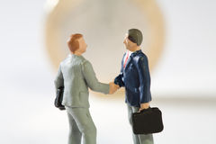Agreement On New EU Fiscal Proposals. Two miniature models of businessmen shake hands on top of a Euro coin, conceptual Stock Image