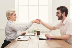 Agreement of young business partners in office. Young business partners work in modern office. Shake hands as a sign of good deal, success and agreement concept Stock Images