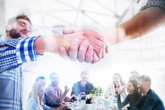 Handshaking business person in casual wear in the office. concept of teamwork and partnership. double exposure. Agreement between young business people with royalty free stock images