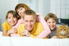 Agregado familiar com quatro membros em uma cama imagem de stock