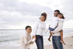 Agregado familiar com quatro membros feliz do African-American na praia foto de stock