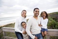 Agregado familiar com quatro membros feliz do African-American na praia Fotografia de Stock