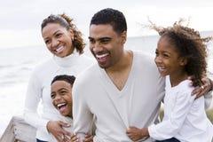 Agregado familiar com quatro membros feliz do African-American na praia