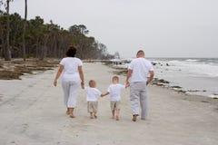 Agregado familiar com quatro membros na praia imagens de stock