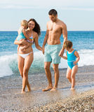 Agregado familiar com quatro membros na praia Fotografia de Stock