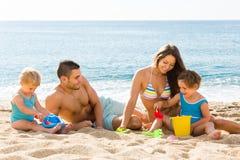 Agregado familiar com quatro membros na praia Imagem de Stock