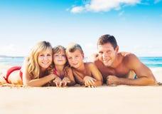 Agregado familiar com quatro membros na praia tropical foto de stock