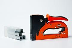 Agregado familiar do grampeador, novo, alaranjado, seguro com grampos Foto de Stock Royalty Free