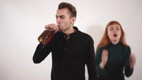 Agressief dronk de mens met bouttle van alcohol het drinken van een fles en verstoren jonge vrouw die met lang rood haar schreeuw stock videobeelden
