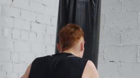 Agressieve bokser bij de intensieve opleiding Hij oefent ponsen met ponsenzak uit stock video