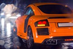 Agressieve en brutale oranje sportwagen op geregend wegbeeld nuttig voor achtergrond Stock Foto's