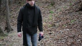 Agressieve jonge mens die die alleen in bos lopen, met het leven, teleurstelling wordt geërgerd stock footage