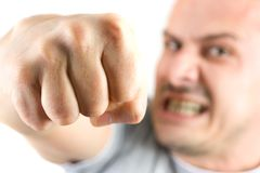 Agressieve mens die zijn vuist toont die op wit wordt geïsoleerde Stock Afbeeldingen