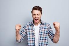 Agressieve mens in geruit overhemd met opgeheven vuisten en open mou stock afbeelding