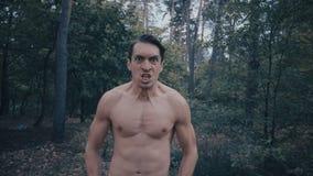 Agressieve Mens met een naakt torso die woedend in het bos gillen stock videobeelden