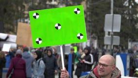 Agressieve protesteerder op staking met groene affiche in handen Revolutie in stad tijdens dag stock video