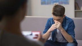 Agressieve tiener die aan psycholoog, het bezoeken rehab zitting, onhandige leeftijd spreken stock videobeelden