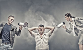 Agression in communication. Furious people screaming agressively in megaphone at man stock images