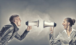 Agression in communication. Furious women screaming agressively in megaphone at man royalty free stock image