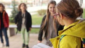 Agression et cruauté de l'adolescence Les despotes approchent la fille et la poussent, courses d'écolière loin banque de vidéos