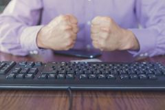 Agression in the Internet, man sitting behind keyboard with hands fists clenched. Front view, dim image royalty free stock photography