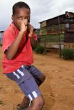 Agressive african boy. Boy taking in a aggressive pose. Children grow up in bad economic and political environments in South African townships. During the latest stock photography