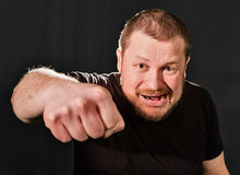 Agressive bully threatens with a fist. Portrait low key Royalty Free Stock Image