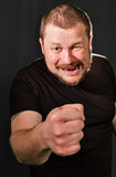 Agressive bully threatens with a fist. Portrait low key Royalty Free Stock Photos