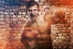 Agressive guy in a boxing gloves Stock Photography