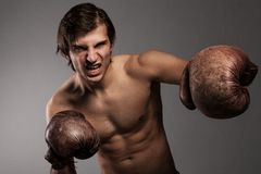 Agressive guy in a boxing gloves Royalty Free Stock Photography