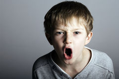 An agressive little boy shouts. At the camera Royalty Free Stock Image