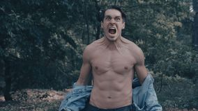 Agressive Man with a naked torso furiously screaming in the forest