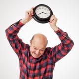 Agressive man ruins clocks. Man breaks the clock in panic because of the deadline Stock Image